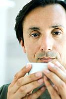 Man holding cup, looking at camera, portrait