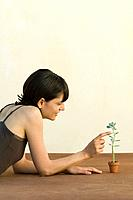 Woman lying on the ground, touching small succulent plant