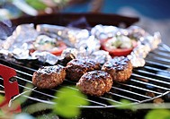 Meatballs and tomatoes in foil on a barbecue