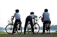 Teenagers on their bicycle watching the Mekong river, Vientiane, Laos