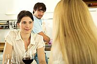 Three young people drinking wine in kitchen, close_up
