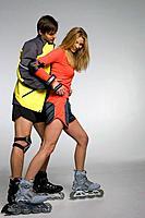 Young couple inline skating, studio shot