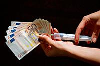 Close_up of syringe being injected into 50 Euro notes