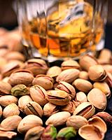 Closed Up Image of Several Pistachios Next to A Glass With Beer, Differential Focus