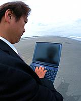 Closed Up Image of a Businessman Using a Laptop at the Beach, High Angle View, Side View, Fish Eye