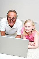 Grandfather and granddaughter 8_9 lying on floor, using laptop, portrait