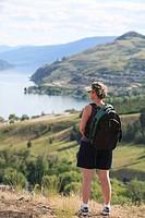 Female hiker overlooking Kalamalka Lake, Vernon, British Columbia, Canada.