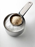 Granulated white sugar and unrefined cane sugar in measuring cups stacked editorial food