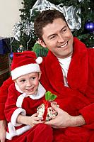 Man with arm around boy 5_6 in Santa hat holding Christmas present