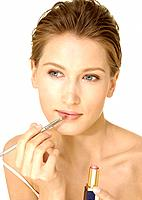 Close_up of a young woman applying lipstick with a lip brush