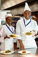 African chefs holding plates of food