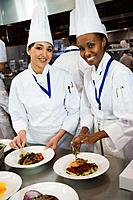 Multi_ethnic female chefs garnishing plates of food