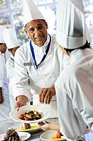 African chef handing plate of food