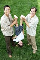 Two men holding little boy upside down by his legs, all smiling, high angle view
