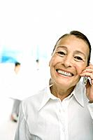 Senior woman using cell phone, smiling at camera