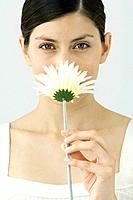 Woman smelling flower, looking at camera, portrait
