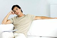 Man relaxing on sofa, looking at camera, leaning on elbow