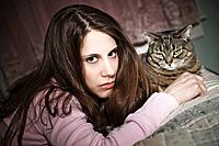 Young woman, with her pet cat, lying on her bed.