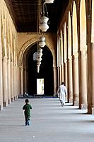 Man and boy walking inside the Mosque of Ahamed ibn Tulun, Cairo, Egypt