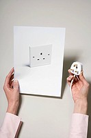 A woman holding a photograph of a socket and a plug