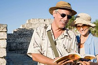 Couple by ruins with guidebook