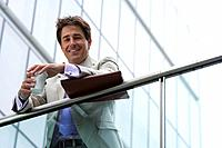 Businessman with disposable cup, smiling, portrait, low angle view