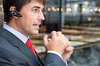 Businessman on mobile phone hands free device, close-up