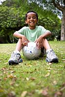 Boy 6-8 with football, smiling, portrait