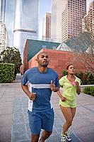 African couple jogging on city sidewalk