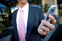 Businessman checking text messages on cell phone
