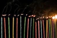 Illuminated candle amid extinguished candles