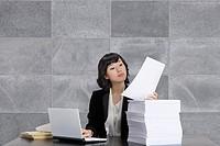 Businesswoman using laptop, reading documents