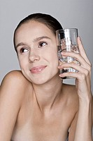 Young woman holding glass, close_up