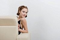 Close_up of young woman sitting on sofa, portrait
