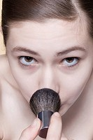 Young woman applying make_up brush, portrait