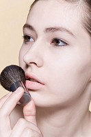 Young woman holding make_up brush, close_up