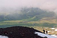 Two skiers climbing Mount Vsevidov in the Aleutian islands above green tundra