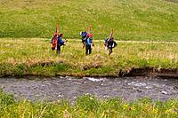 Three skiers hiking in grass on Umnak Island in the Aleutian Islands Alaska