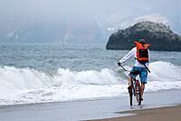 A man riding a cruiser bike on the beach in San Francisco on a foggy day