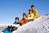 Four smiling friends sitting in the snow on a sunny day at Northstar ski resort in California
