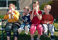 kids eating apples on bench