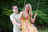 Man pushing girlfriend on swing