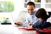 Son Doing Homework as Father Uses Laptop