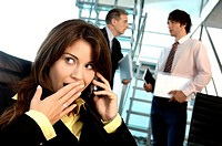 Businesswoman using mobile phone in office with colleagues in background