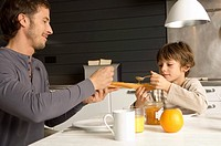 Mid adult man and his son having breakfast