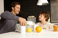 Mid adult man having breakfast with his son in the kitchen