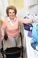 Senior woman with laundry by washing machine