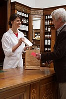 Female pharmacist packing drugs for a customer
