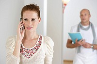 Young woman phoning with a mobile phone, mature man in background