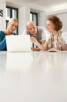 Three businesspeople using laptop while a meeting